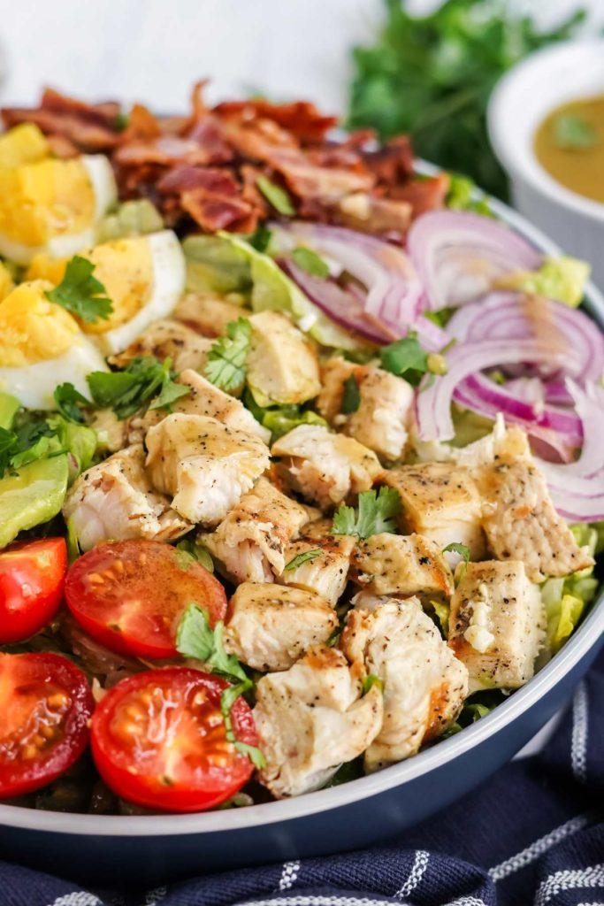 chicken cobb salad in a blue bowl.