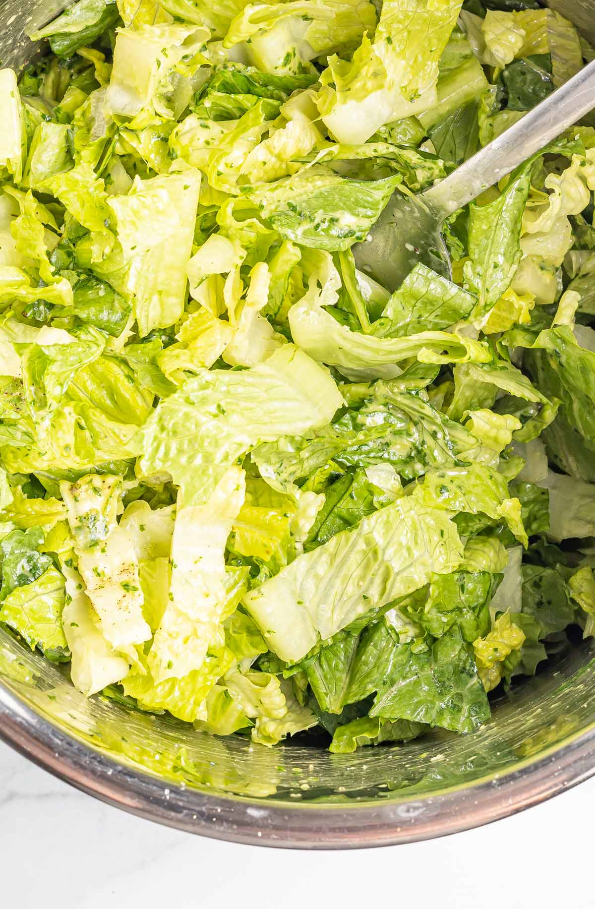 the salad being tossed to together.