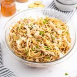 sesame noodles with chicken in a bowl.