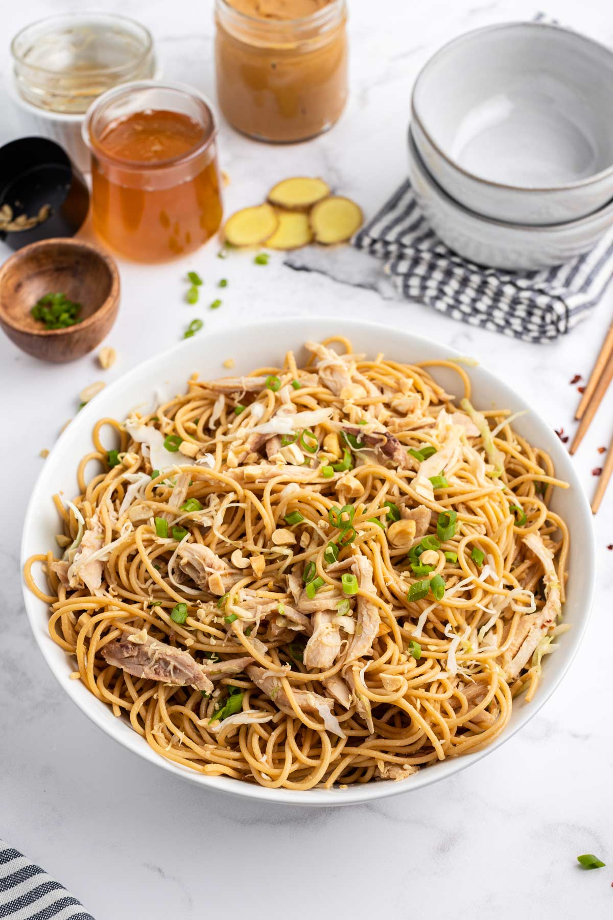 chicken sesame noodles in a white bowl.