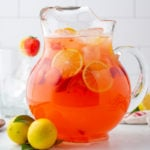 a pitcher of lemonade with glasses in the background.