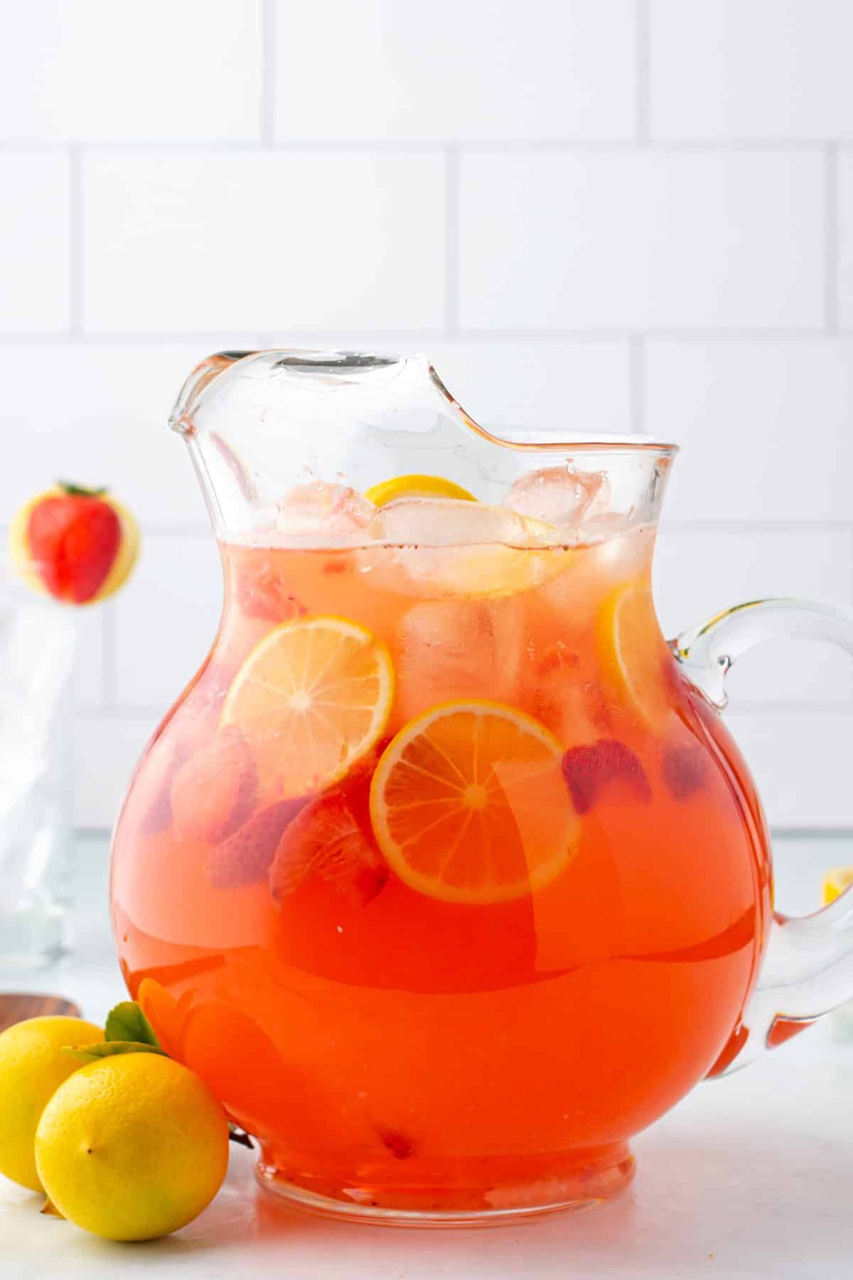 a pitcher of lemonad flavored with strawberries.