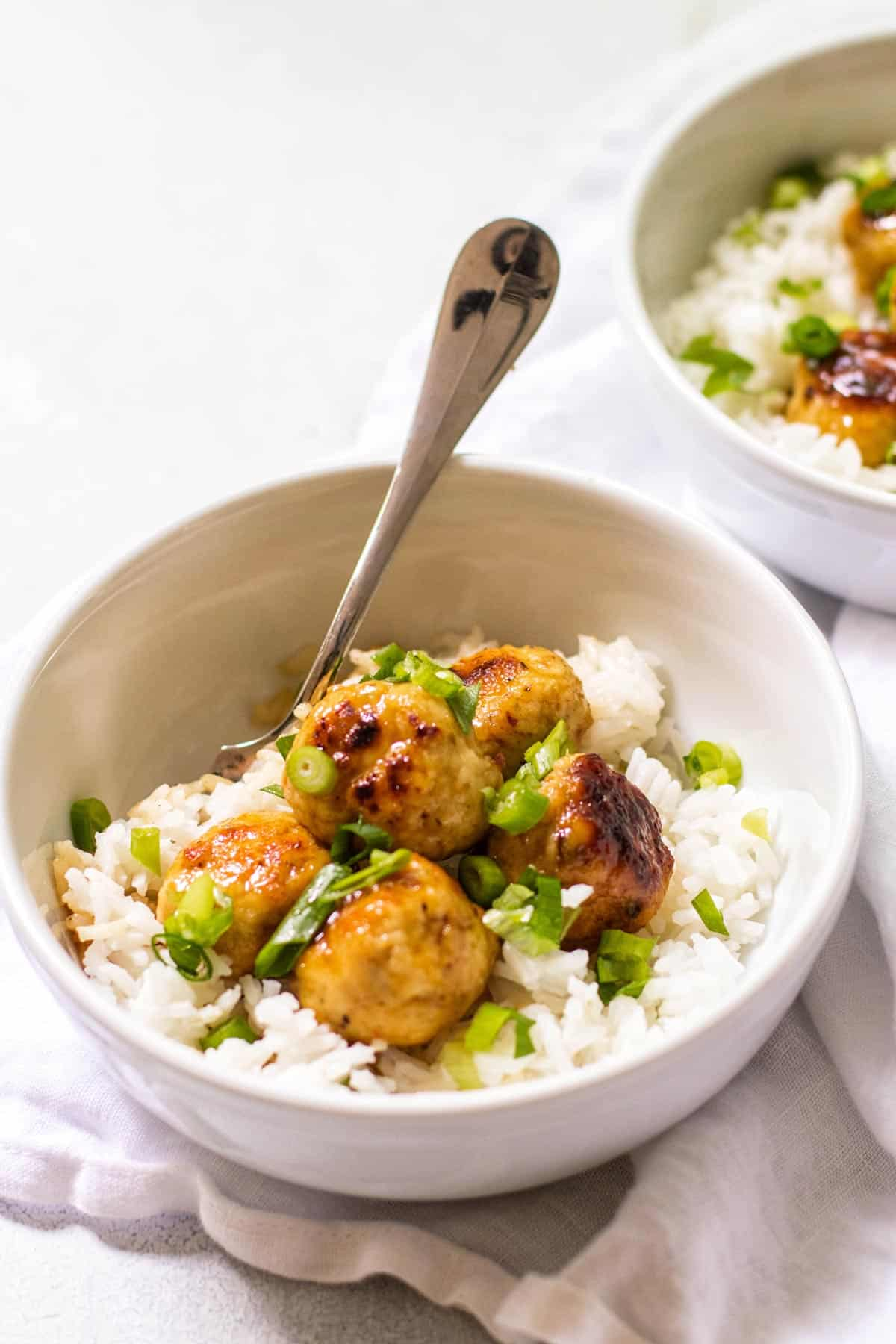 a bowl with rice and orange chicken meatballs.
