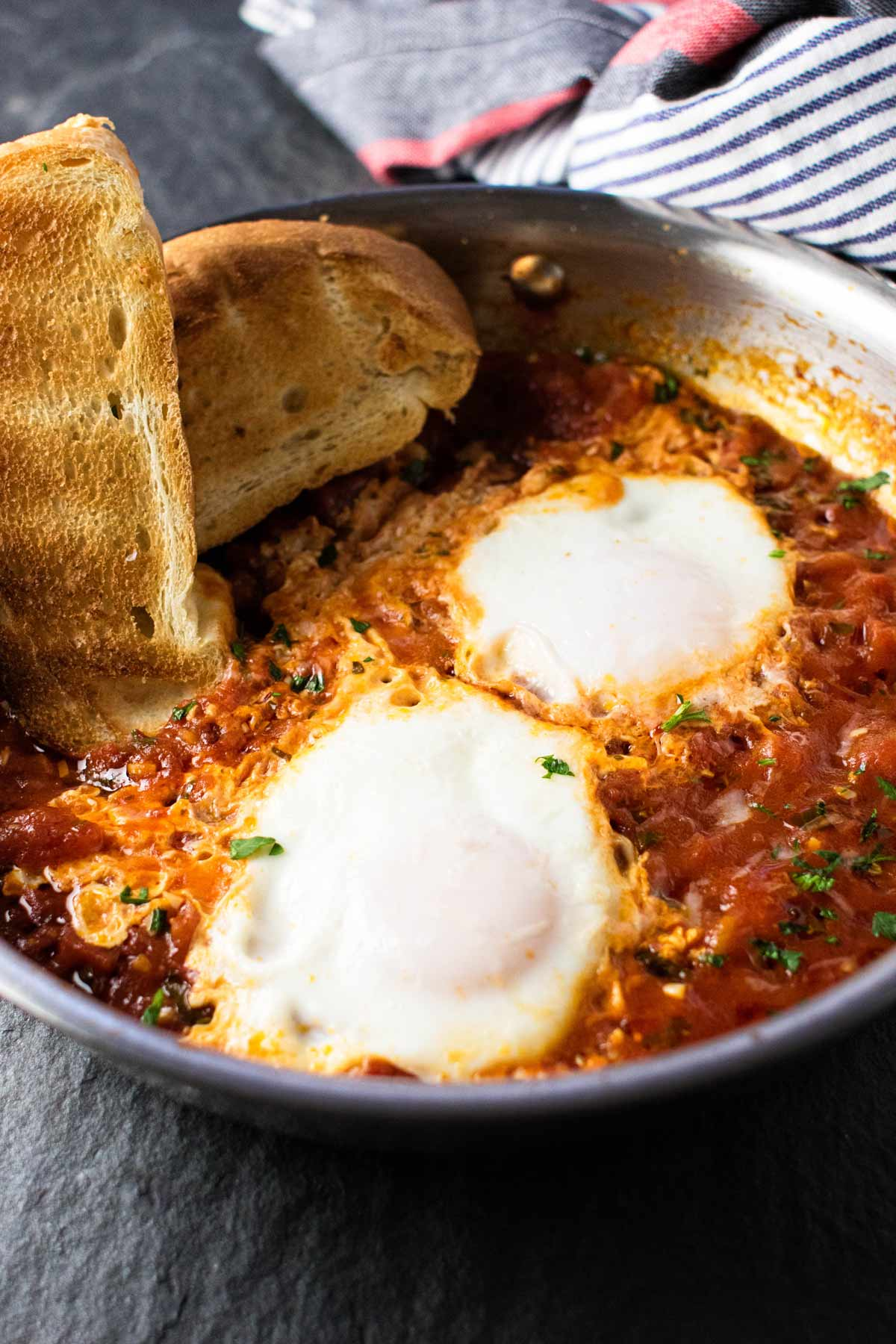 two eggs in a skillet with spicy tomato sauce.