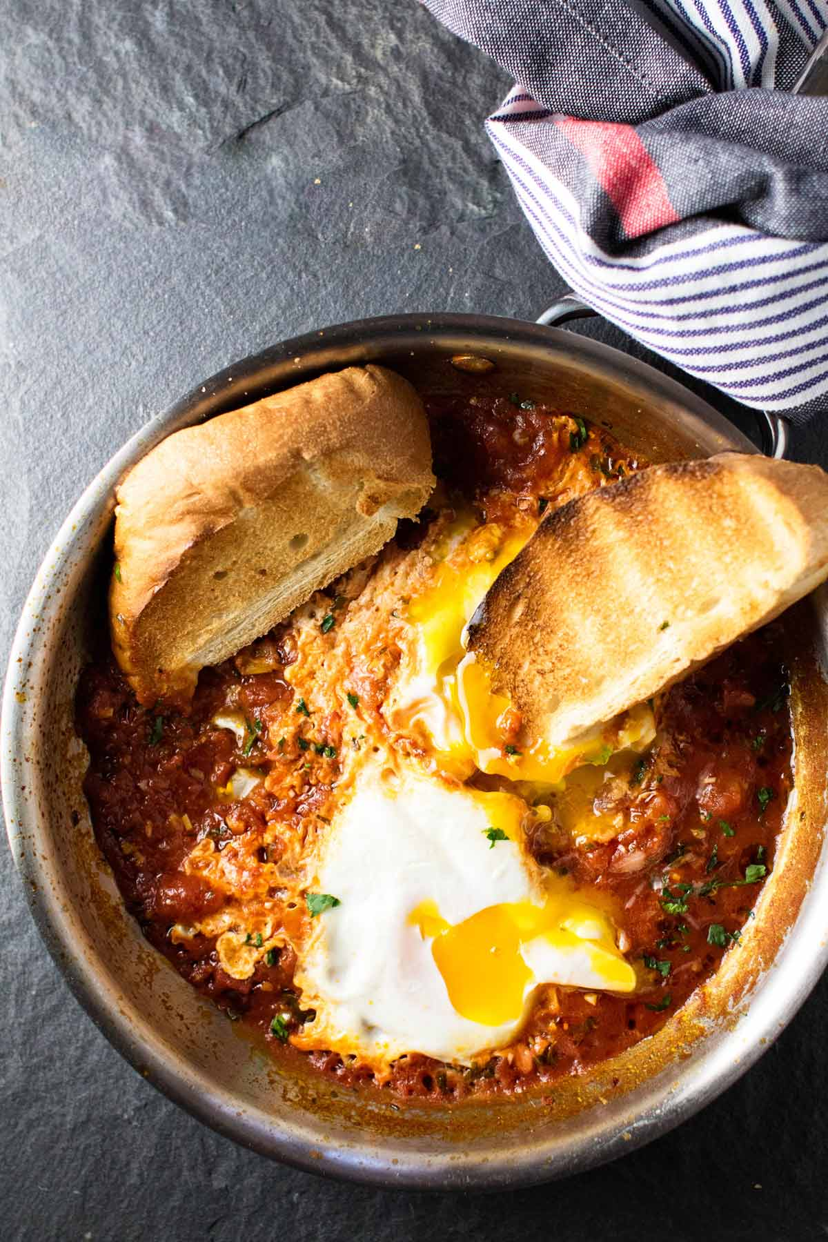 Two pieces of toast with eggs in purgatory in a skillet.