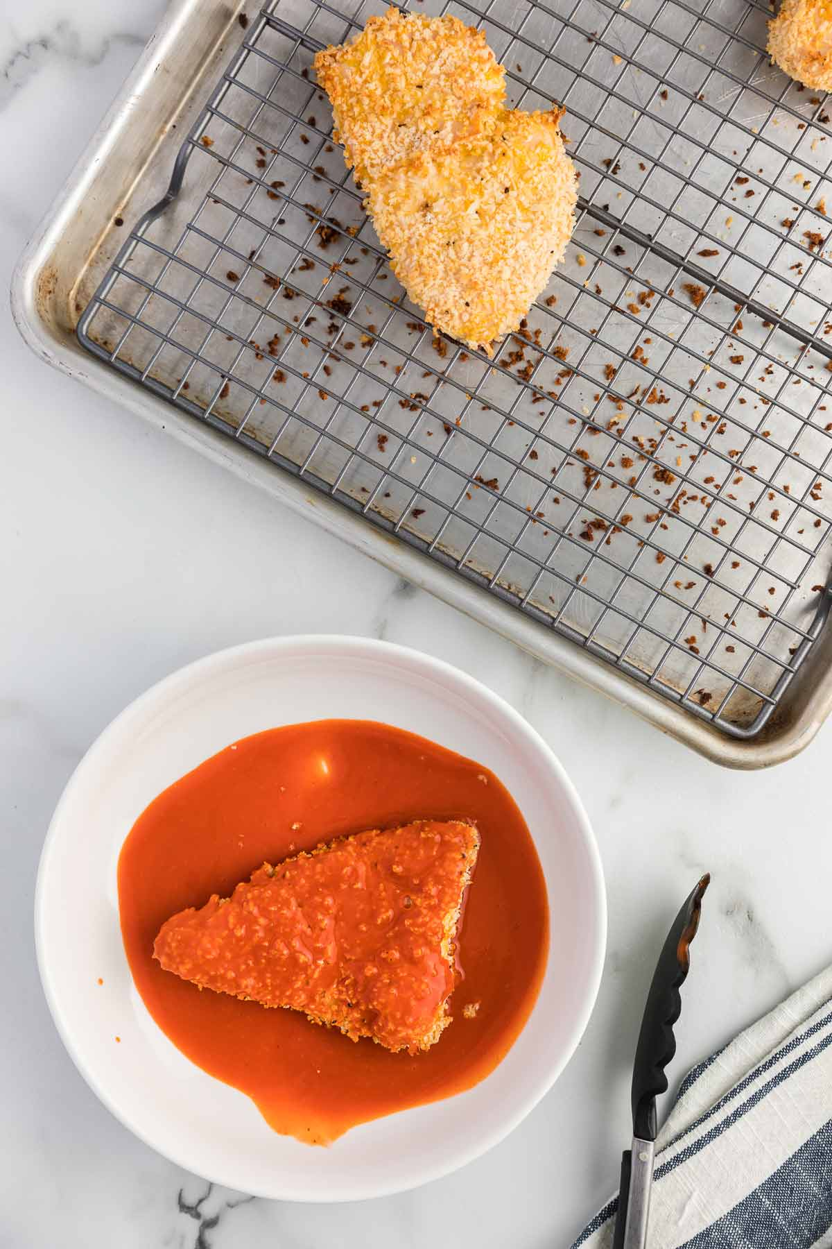 breaded chicken being coated in buffalo sauce.