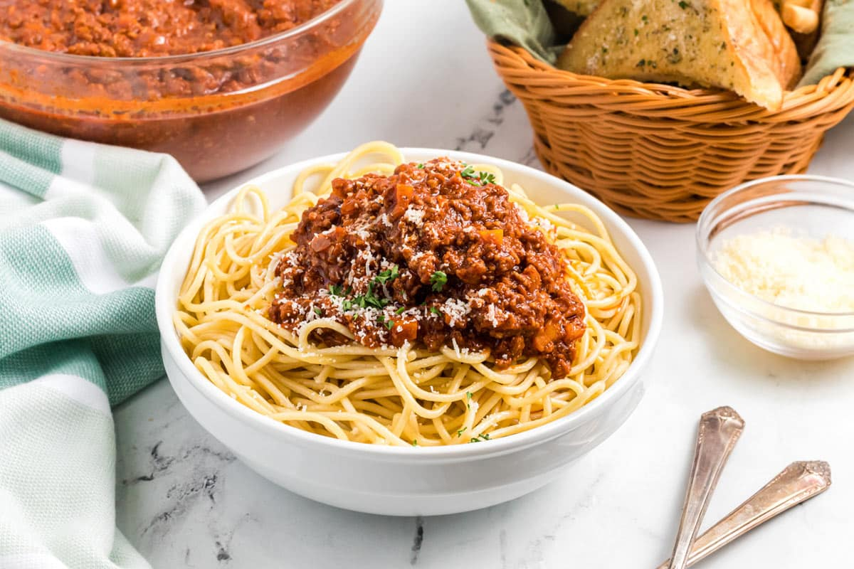 a bowl of pasta topped with sauce.