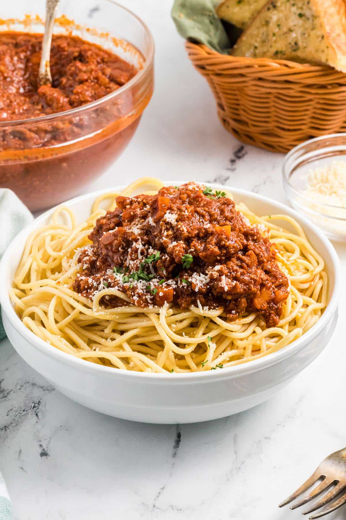 a bowl of spaghetti topped with bolognese.